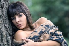 A young and beautiful woman with bare shoulders wrapped in her shawl,. Young Italian woman with naked shoulders wearing a shawl leaning against a tree in a Stock Photo