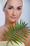 Young beautiful woman after bath touching face green plants Stock Photography