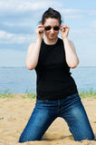 Young beautiful woman on the beach. Young beautiful woman in sunglasses on the beach stock photo