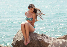 Young beautiful woman on the beach. Young Asian girl sitting on the stone exterior of the sea Stock Image