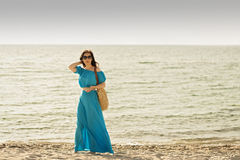 Young beautiful woman on the beach in azure long dress with mobi Royalty Free Stock Photography
