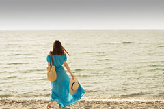 Young beautiful woman on the beach in azure long dress. Stock Images