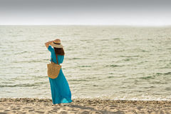 Young beautiful woman on the beach in azure long dress. Stock Photo