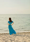 Young beautiful woman on the beach in azure long dress. Royalty Free Stock Images
