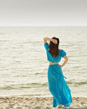 Young beautiful woman on the beach in azure long dress. Stock Image