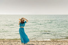 Young beautiful woman on the beach in azure long dress takes pic. Tures of herself on a smartphone. Selective focus Stock Photography