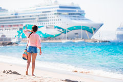 Young beautiful woman on the beach background big cruise ship. Royalty Free Stock Photo