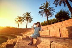 Young beautiful woman in beach hat sitting on the steps of an ancient amphitheater at sunny day in Bodrum, Turkey. Vacation stock photos