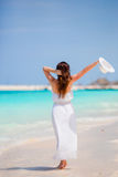 Young beautiful woman on beach vacation. Happy girl enjoy beach and warm weather while walking along the ocean Royalty Free Stock Photo