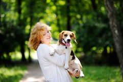 Young beautiful woman with Beagle dog. In the summer park. Loving female owner with her domestic pet Stock Photography