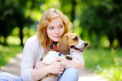 Young beautiful woman with Beagle dog. In the summer park. Loving female owner with her domestic pet Royalty Free Stock Image