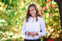 Young beautiful woman. Beauty smiling teenager girl in autumn park Royalty Free Stock Images