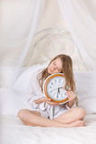 Young beautiful woman in bed and alarm clock Stock Images