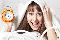 Young beautiful woman in bed with clock Stock Photo