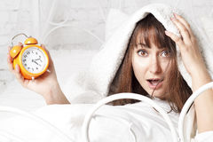 Young beautiful woman in bed with clock Stock Photography