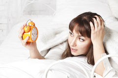Young beautiful woman in bed with clock Stock Photos
