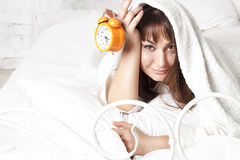 Young beautiful woman in bed with clock Royalty Free Stock Image