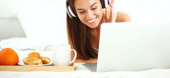Young beautiful woman in bed listening to music Stock Photography