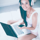 Young beautiful woman in bed listening to music Royalty Free Stock Photo