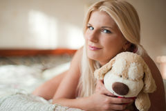 Young beautiful woman on the bed with a toy Royalty Free Stock Image