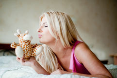 Young beautiful woman on the bed with a toy Royalty Free Stock Photo