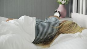 Young beautiful woman been woken up by phone call in the morning but return to sleep again