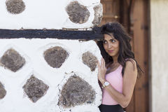 Young beautiful woman behind an old stone wall, outdoor shot Stock Photo