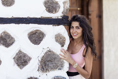 Young beautiful woman behind an old stone wall, outdoor shot Stock Photography