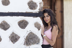 Young beautiful woman behind an old stone wall, outdoor shot Stock Image