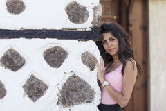 Young beautiful woman behind an old stone wall, outdoor shot Royalty Free Stock Photography