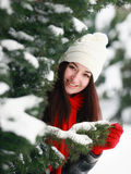 Young beautiful woman behind snow covered pine Stock Photo