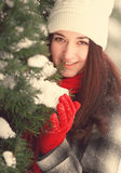 Young beautiful woman behind snow covered pine royalty free stock photography