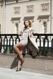 Young beautiful woman in beige coat posing outdoors in sunny wea Royalty Free Stock Photo