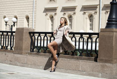 Young beautiful woman in beige coat posing outdoors in sunny wea Stock Photo