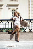 Young beautiful woman in beige coat posing outdoors in sunny wea Royalty Free Stock Photos