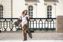 Young beautiful woman in beige coat posing outdoors in sunny wea Stock Image