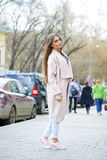 Young beautiful woman in beige coat and torn jeans and pink snea Stock Photography
