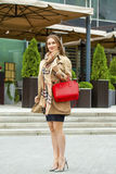 Young beautiful woman in beige short coat posing outdoors in spr Royalty Free Stock Photo