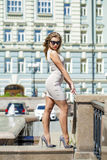 Young beautiful woman in beige short dress posing outdoors in su Royalty Free Stock Photography
