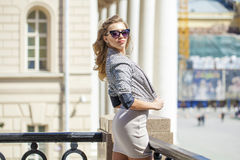 Young beautiful woman in beige short dress posing outdoors in su Royalty Free Stock Image