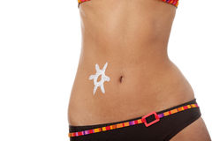 Young beautiful woman belly. Young beautiful woman with sun-shaped sun cream on her belly, isolated on white Stock Photography