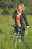 Young beautiful woman with bicycle listening to music Stock Image