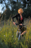 Young beautiful woman with bicycle resting in park Stock Image