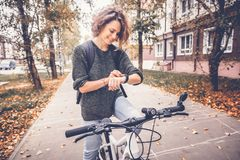 Young beautiful woman on a bicycle uses a smartwatch, navigation Royalty Free Stock Images