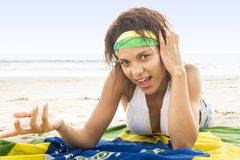 Young beautiful woman in bikini on beach with Brazil flag. Young beautiful woman in bikini on beach lying on Brazil flag Royalty Free Stock Image
