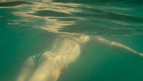 Young Beautiful Woman In Bikini Diving In Blue Sea Underwater, Woman Legs With Protective Shoes Underwater Sea stock footage