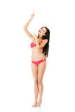 Young beautiful woman in bikini pointing on copy space Stock Images