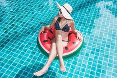Young beautiful woman bikini in ring float inflatable watermelon. On summer holiday swimming pool at resort water blue Royalty Free Stock Images