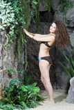 Young beautiful woman in bikini stands near to big rocks Stock Images