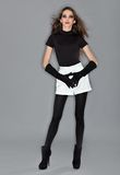 Young beautiful woman in black combi dress. White shorts and velvet gloves, ring flash studio portrait Stock Image